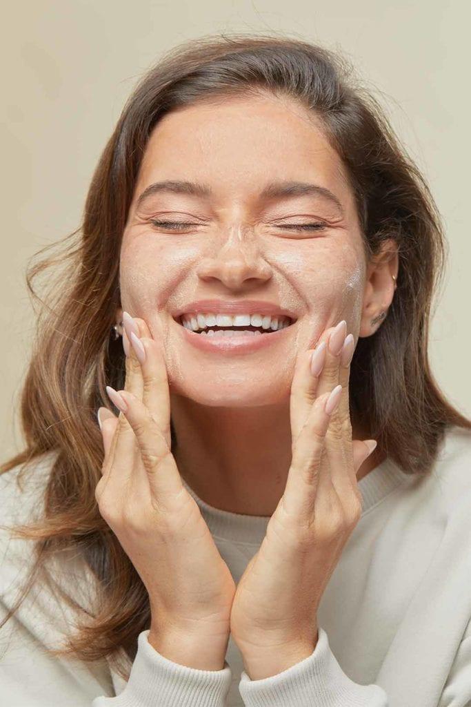 אישה מורחת קרם פנים של קולגן