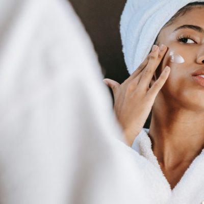 אישה מורחת קרם על עור הפנים שלה